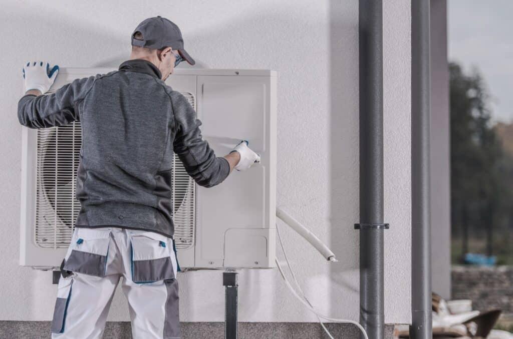 Mann som installerer varmepumpe for noen som ønsker å spare strøm