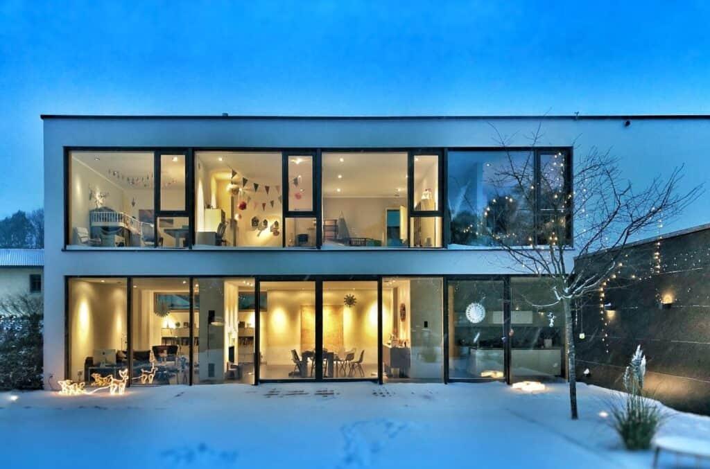 Enebolig med innvendig lys og snø på bakken