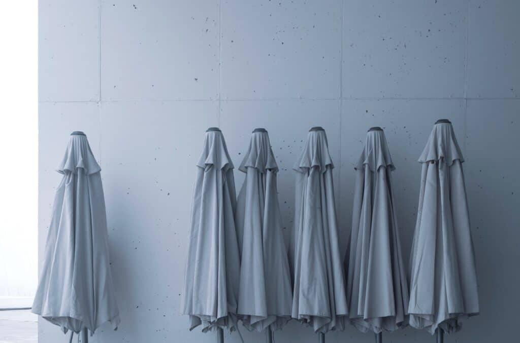 6 parasoller forran hvit vegg