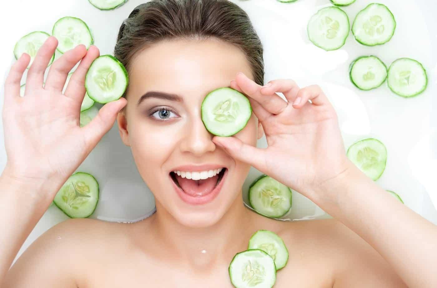 Dame som er på spa med agurk på øynene