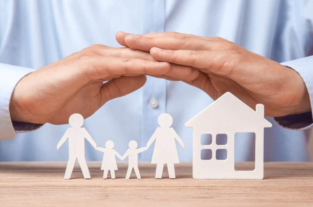 To beskyttende hender over hus og familie som en illustrasjon på forsikring