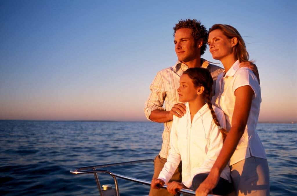 Familie på tre som ser på solnedgangen mens de er på båten sin