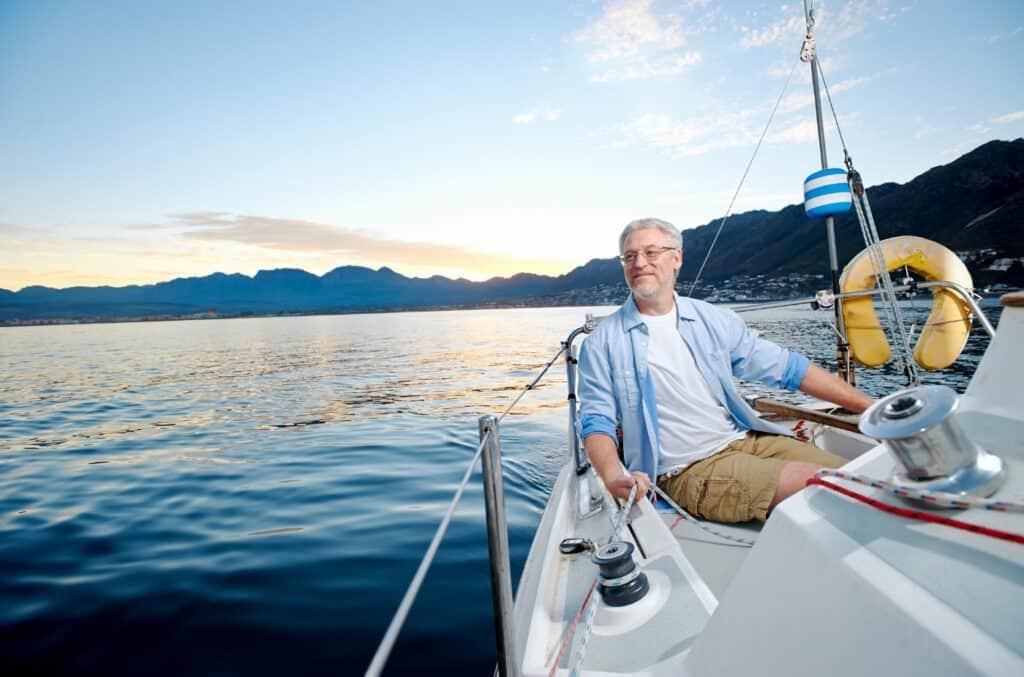 Voksen mann som hygger seg på seilbåten sin fordi han har funnet beste og billigste båtforsikring