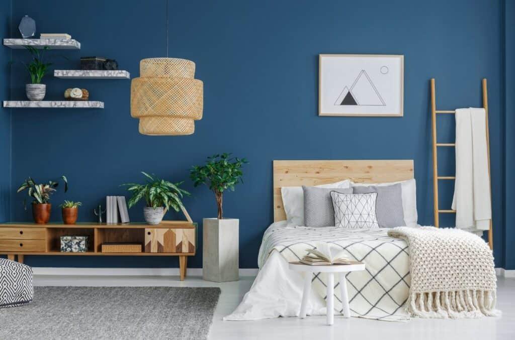 Blå vegg med møbler som seng, bor og hyller
