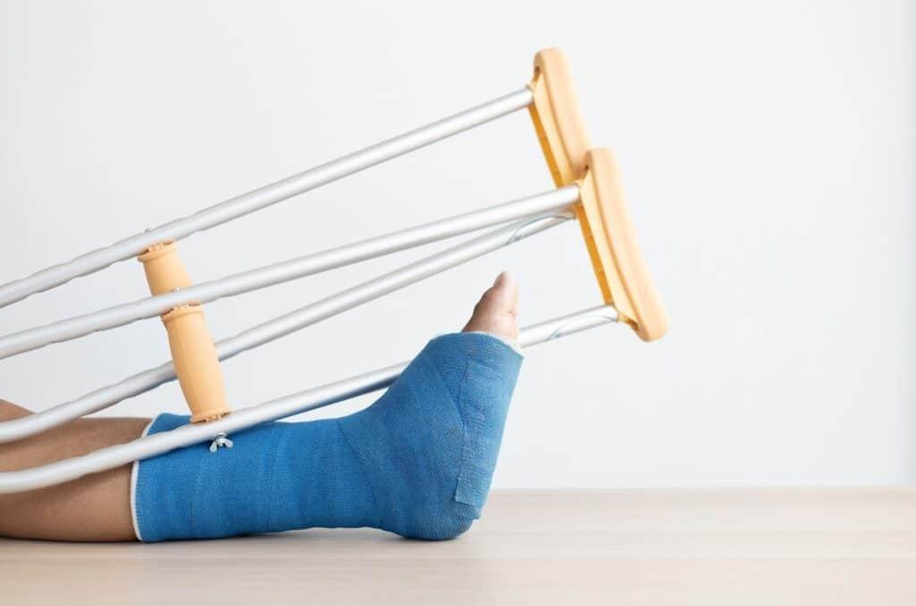 Fot i bandasje med krykker som illustrerer ulykkesforsikring