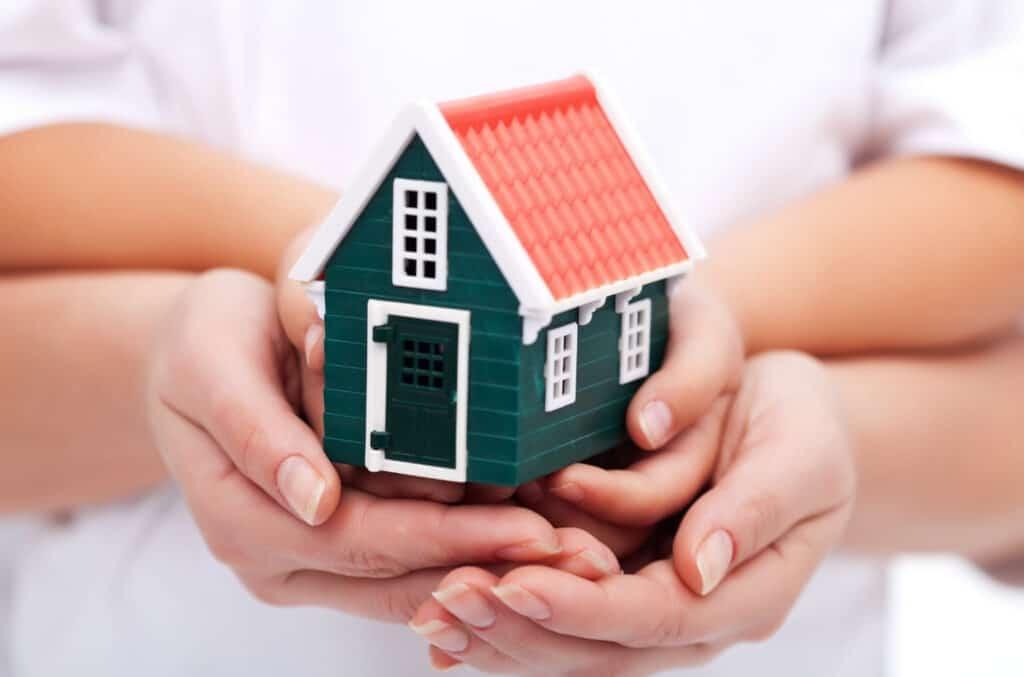 Hender som holder rundt miniatyr hus, som en illustrasjon på husforsikring og boligforsikring