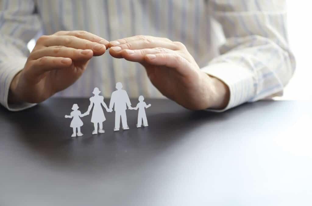 beskyttende hender over familie som illustrerer livsforsikring