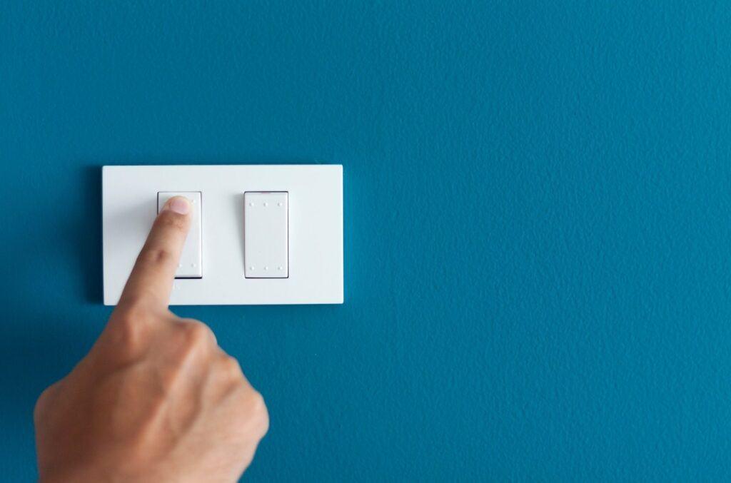 Hånd på lysbryter på blå vegg som illustrerer hvordan man kan bytte strømleverandør